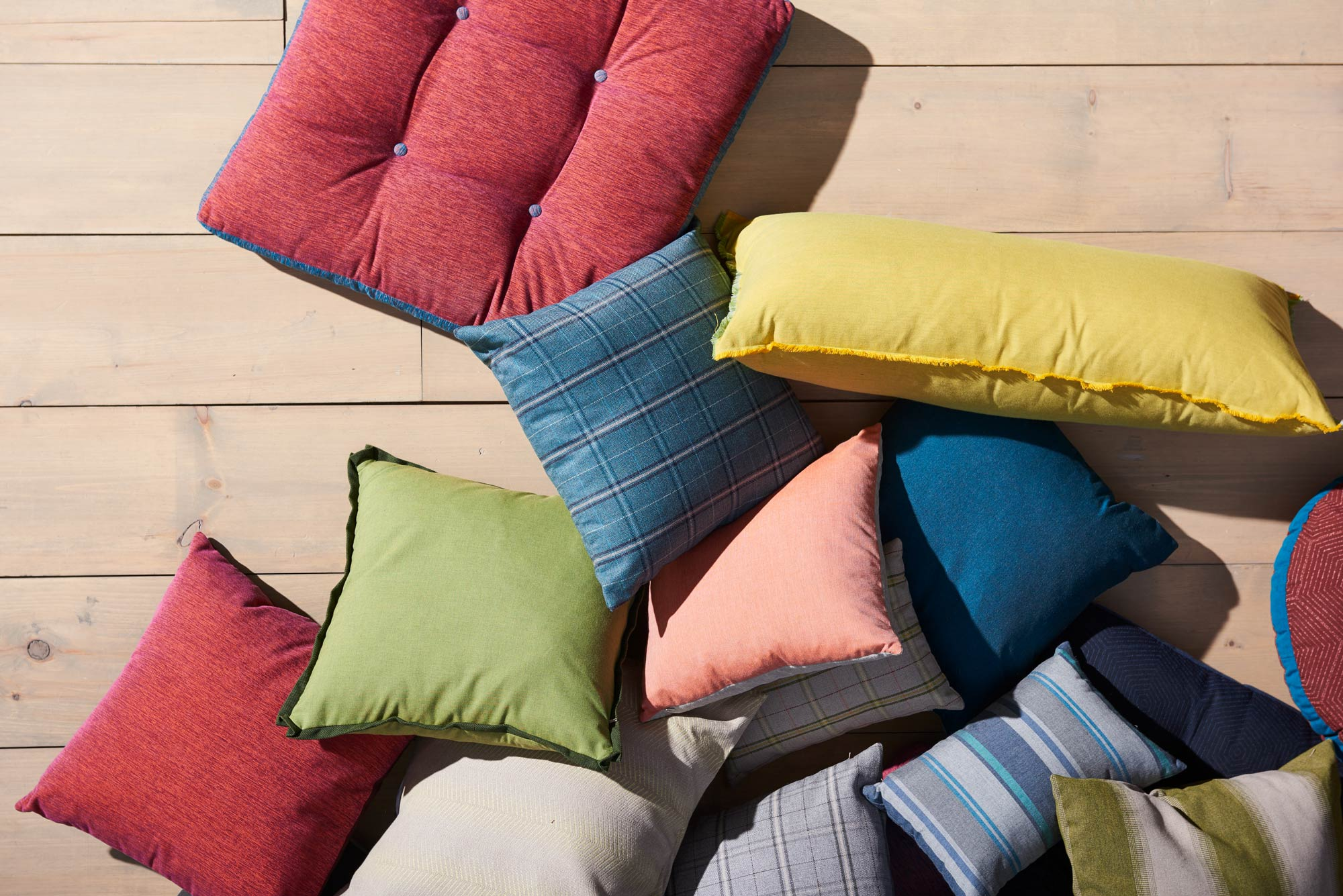 Aerial shot of for scattered throw pillows upholstered in performance fabrics from the Sunbrella Pure Collection.