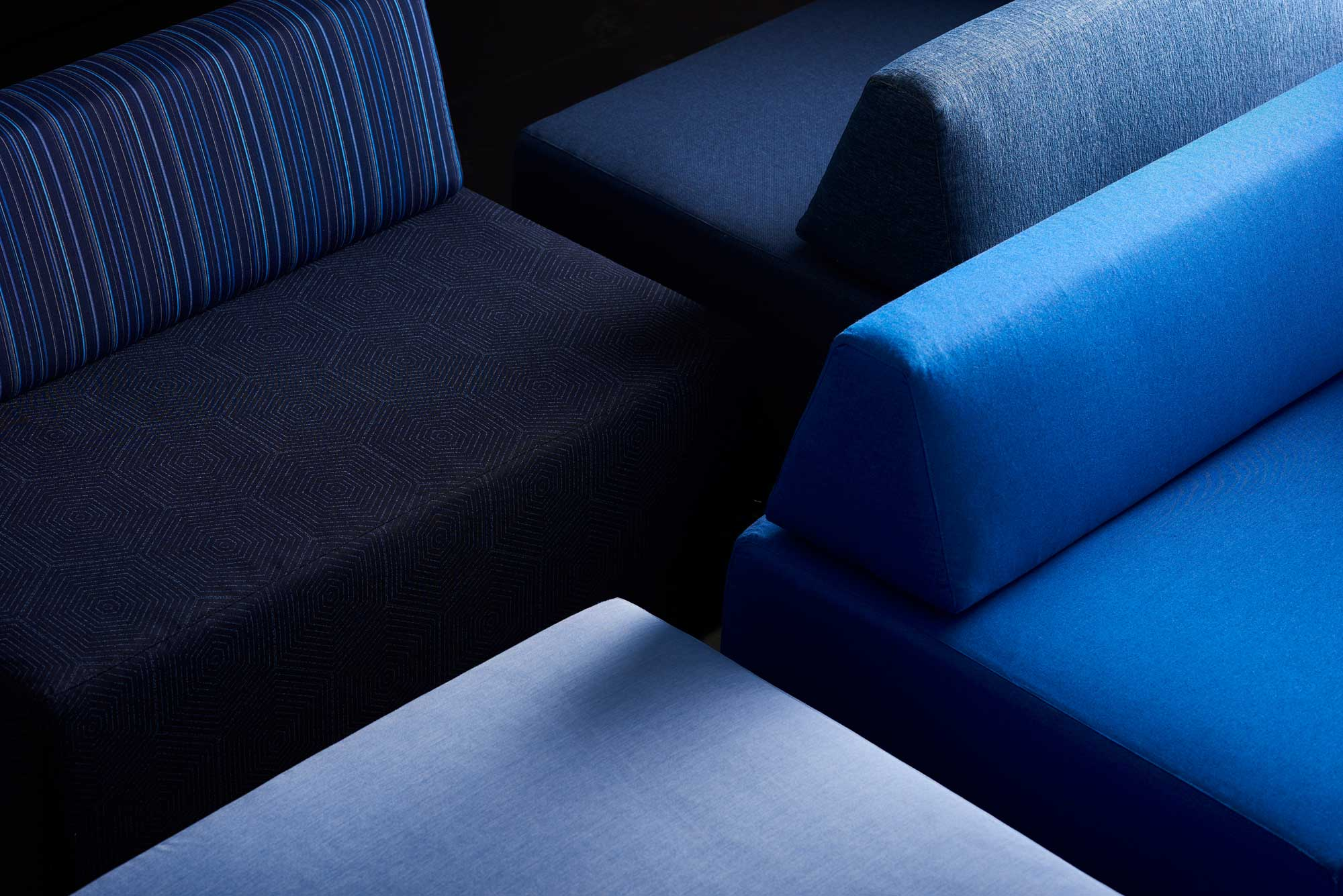 Detail shot of square ottomans and bolster pillows in a blue palette of Sunbrella performance fabrics from the Sunbrella Pure Collection.