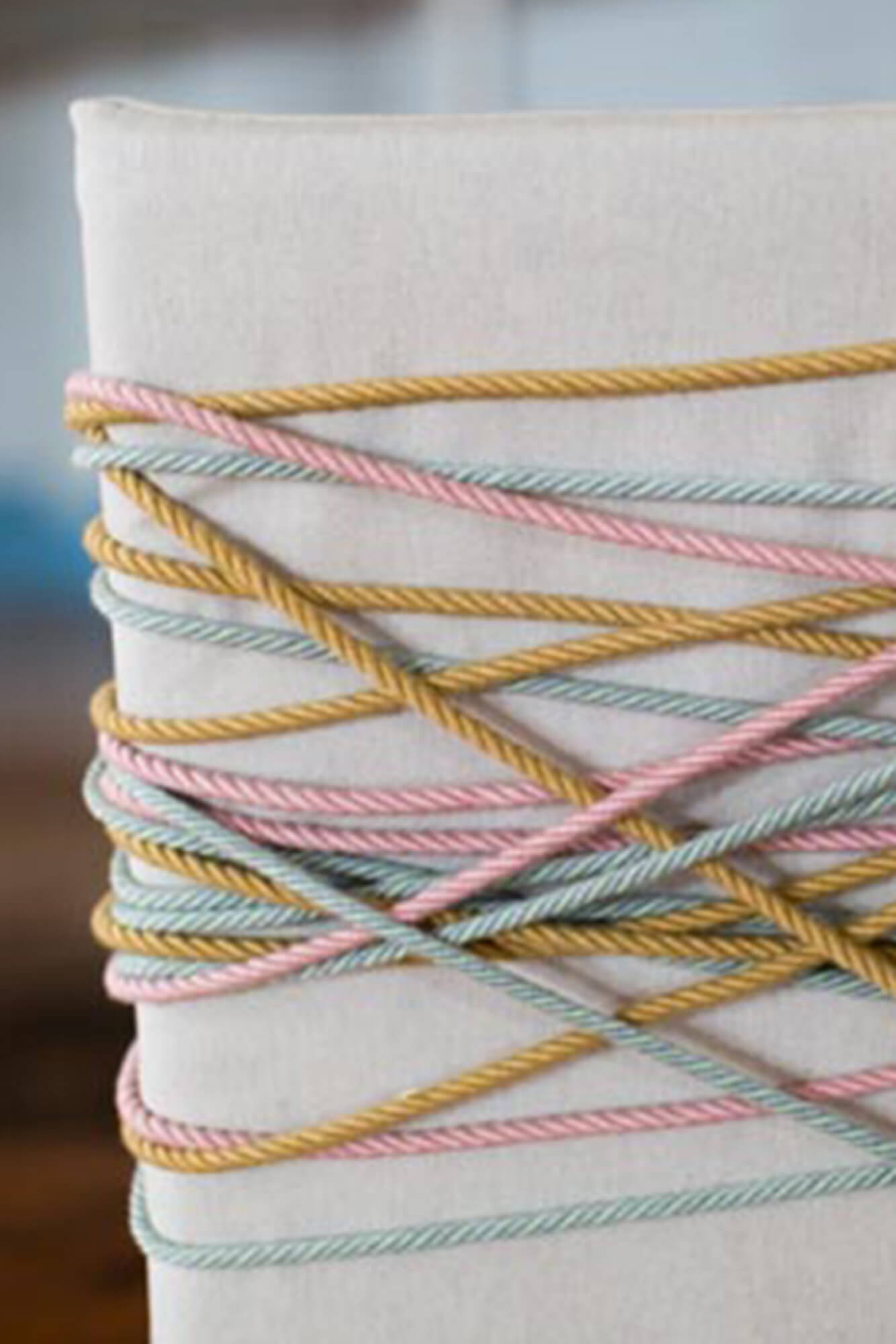 Colorful Sunbrella Rope is artfully wrapped around a beige upholstered chair