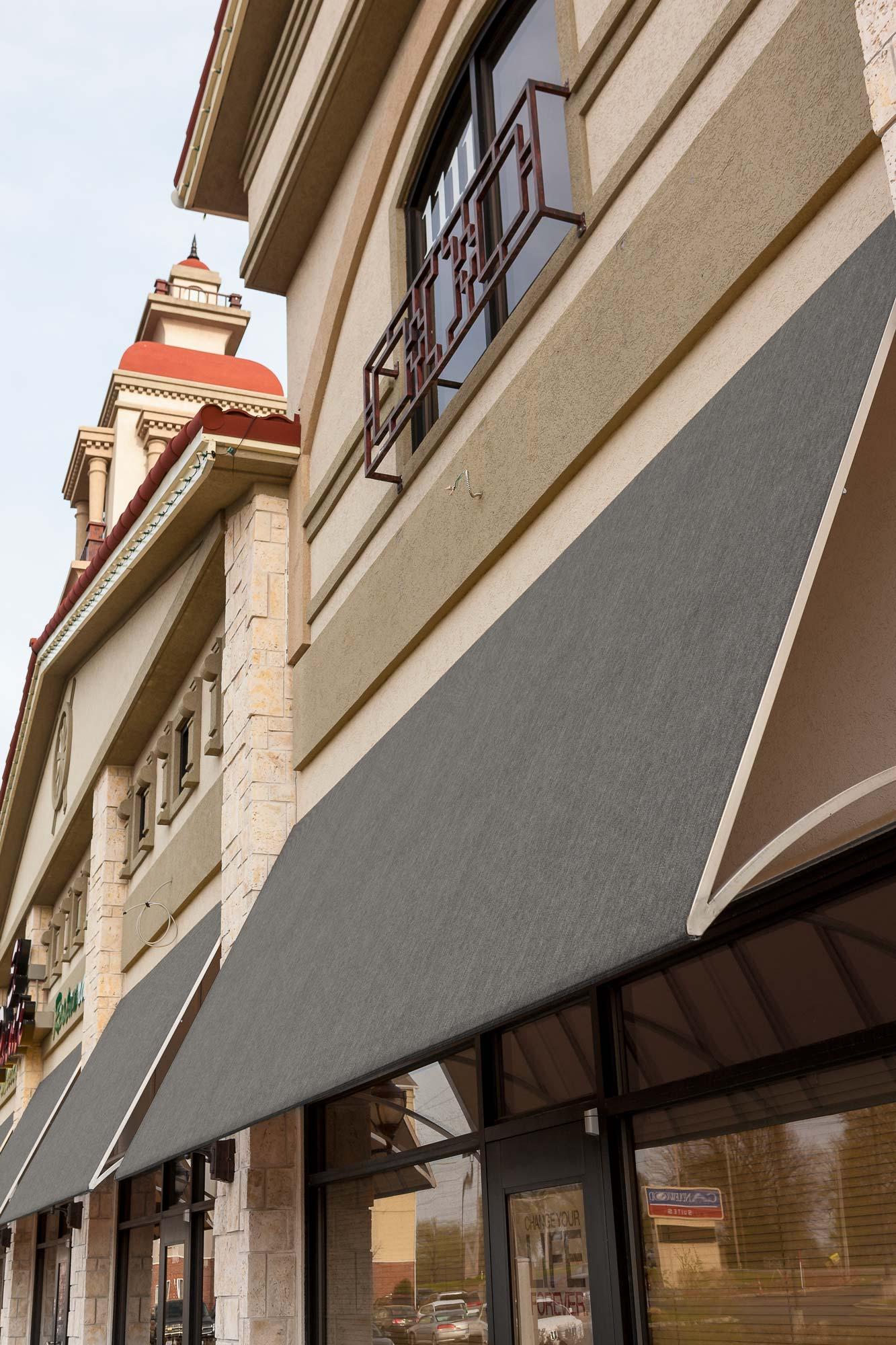 Plan latéral montrant une rangée de vitrines de magasins protégées par des auvents en tissus Sunbrella SeaMark.