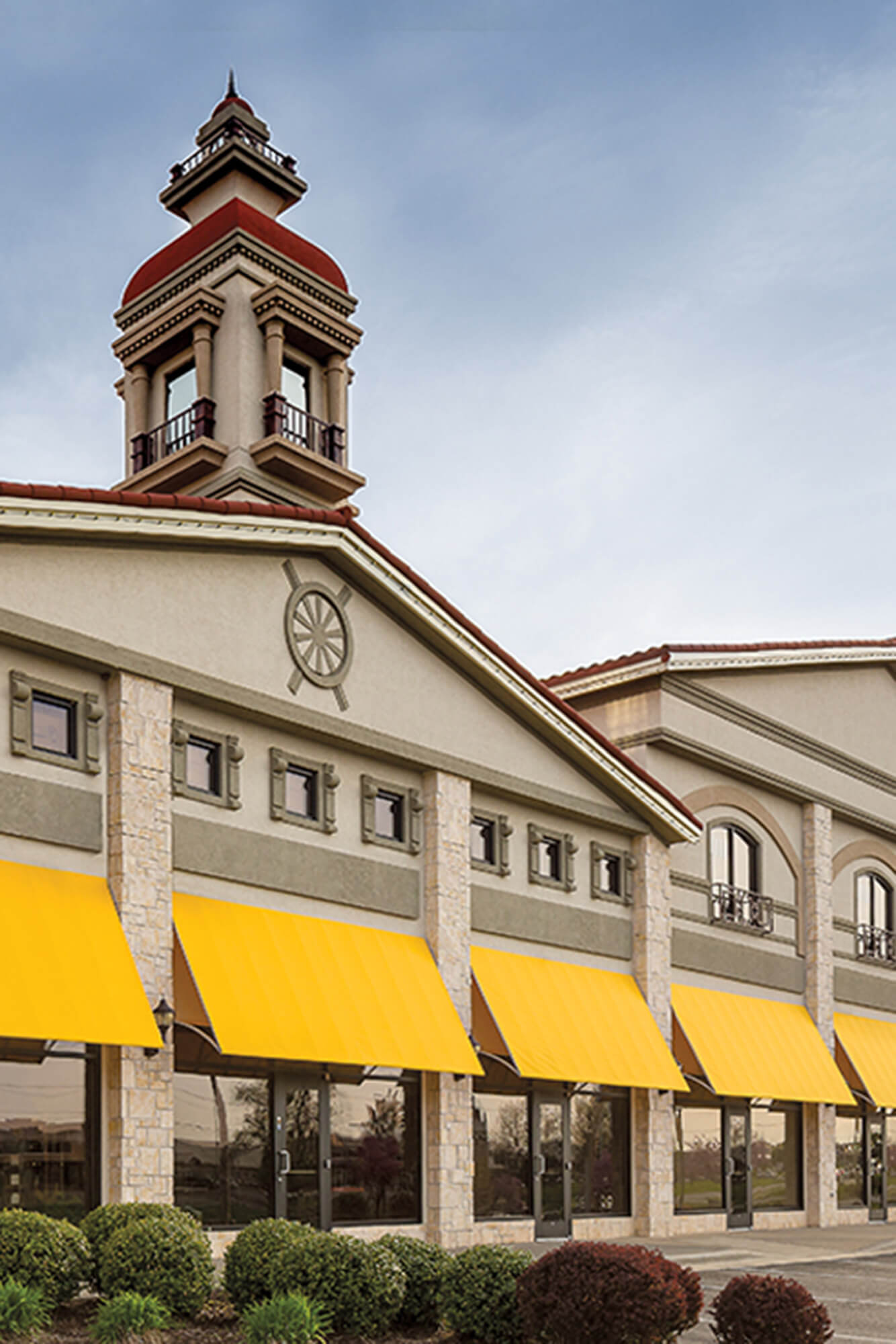 Fixed frame awnings made using yellow Sunbrella Clarity fabric makes a bold statement on a shopping center