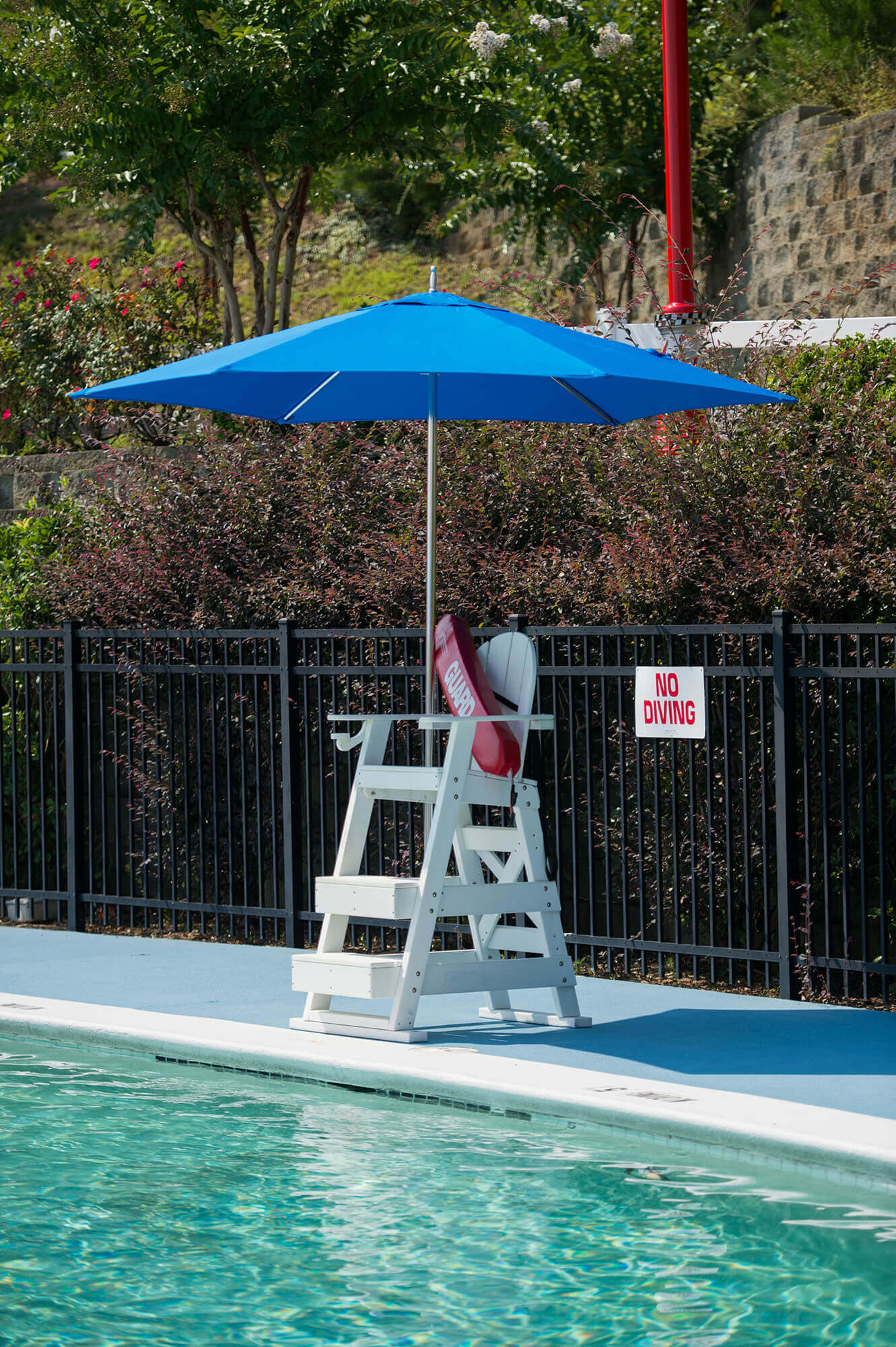 A lifeguard stand is shaded by a bright blue umbrella