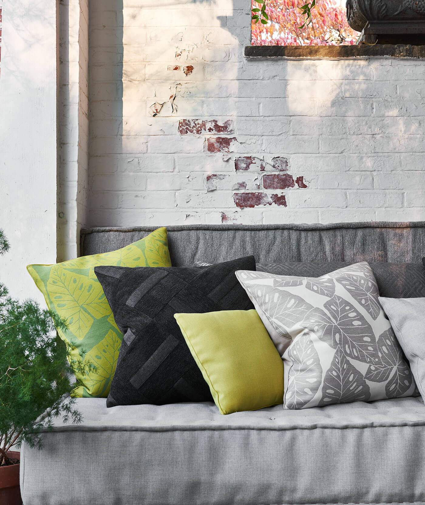 An outdoor room has a seating area of grey cushion with patterned decorative throw pillows