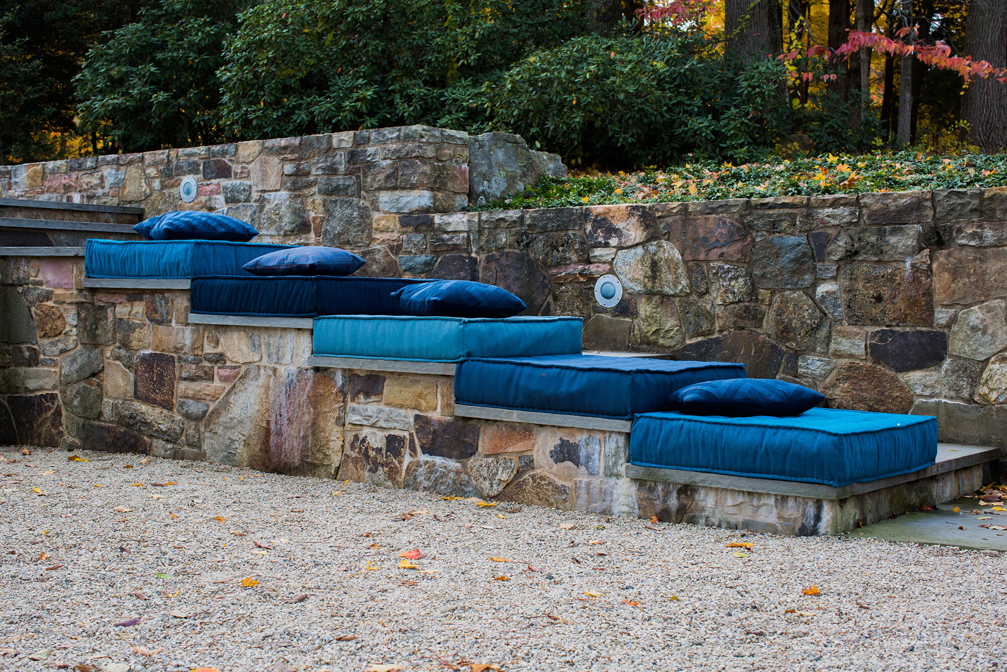 Cushions in hues of blue are stacked on an outdoor stair