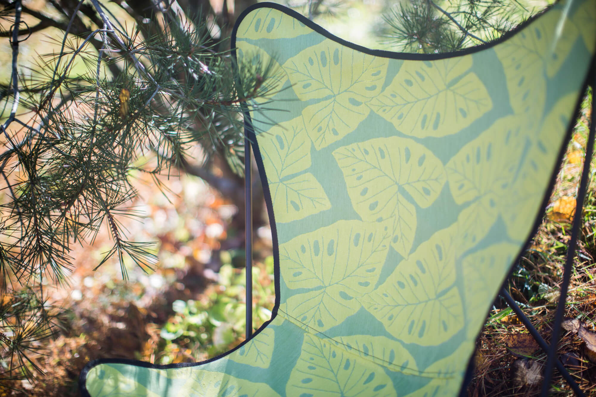 Close up of butterfly chair with Radiant Kiwi fabric from the Sunbrella Shift collection