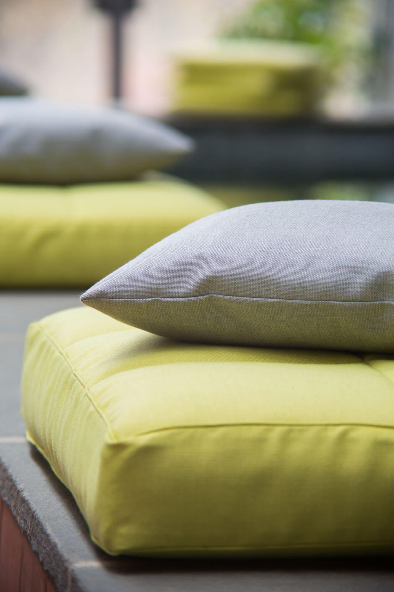 Stacked grey and green pillows made using fabrics from the Sunbrella Shift collection