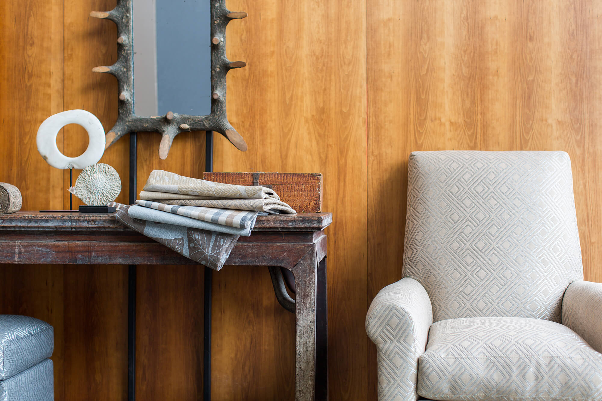 Ghế bọc nệm với hoa văn trung tính cạnh bàn gỗ với chồng vải phía trên