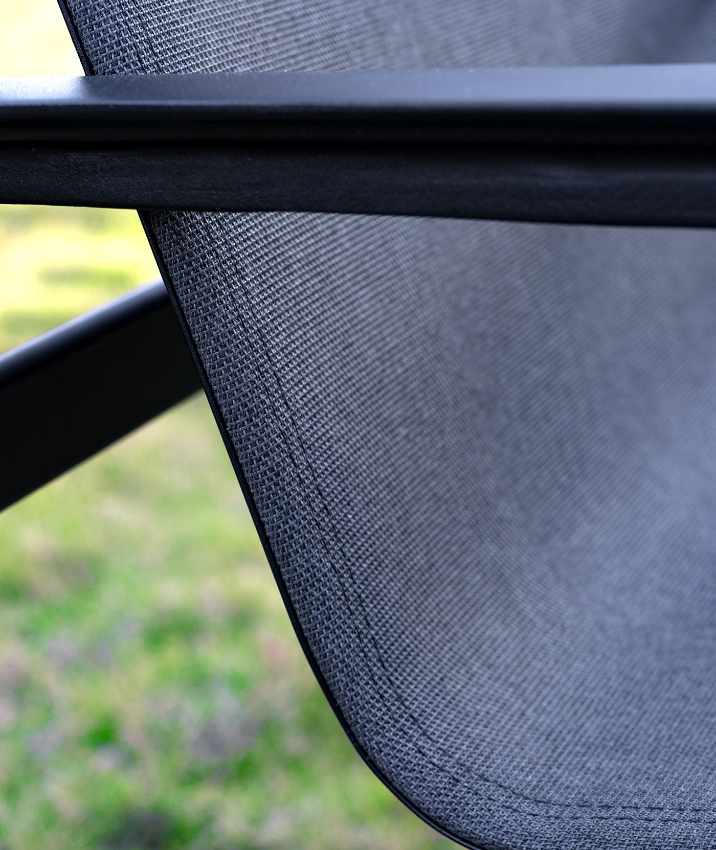 Close up of the seat of a chair made using grey Sunbrella Sling fabric.