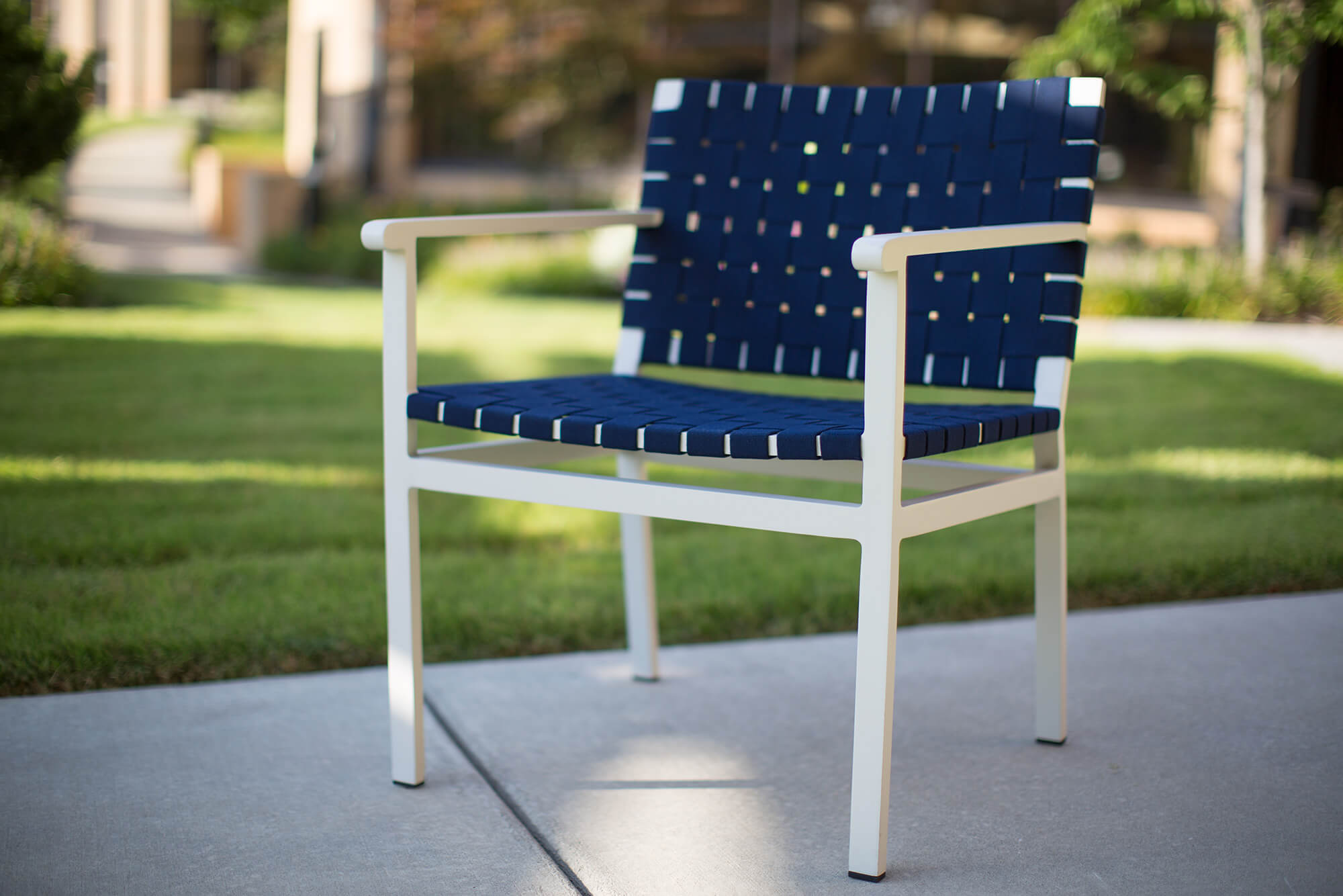 An outdoor chair made using navy Sunbrella Strap sits on a patio