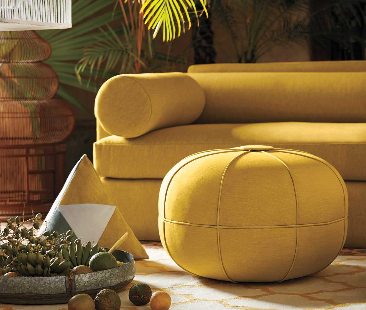 Close-up of the end of a sofa and an ottoman upholstered in yellow Sunbrella performance fabric.