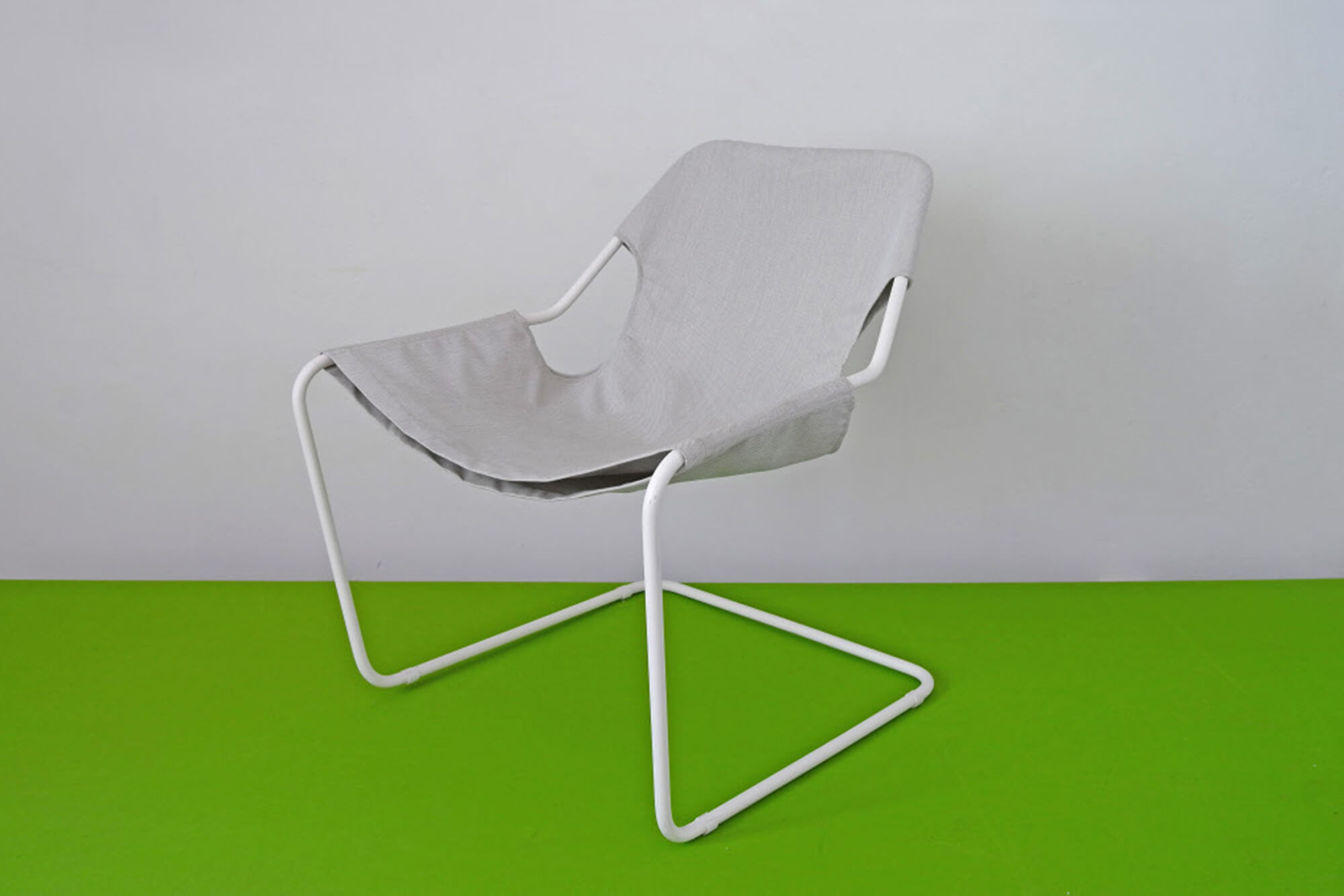 A chair with grey Sunbrella fabrics and a white metal body