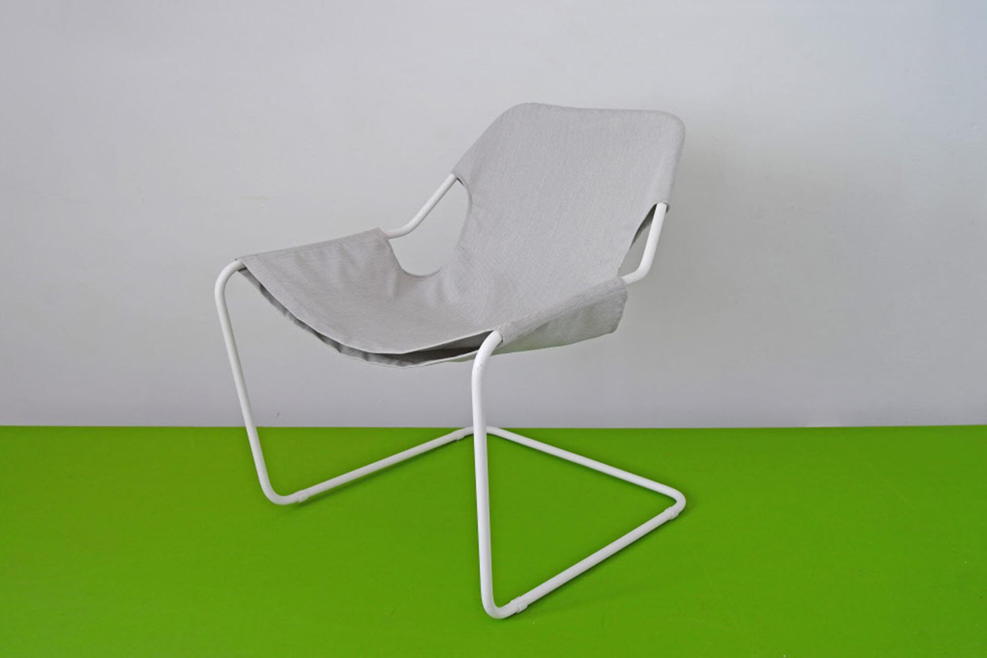 Uma cadeira com tecidos Sunbrella cinza e corpo de metal branco