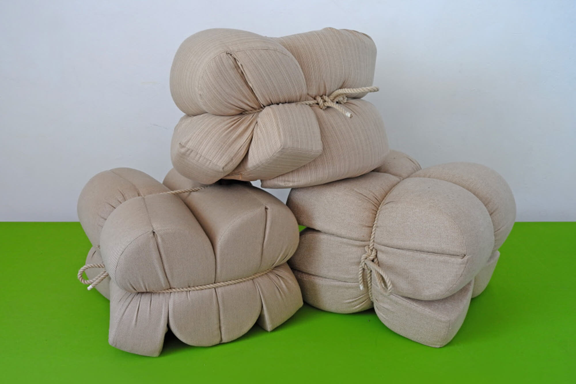 Cushions made using beige Sunbrella fabrics are folded and tied with rope