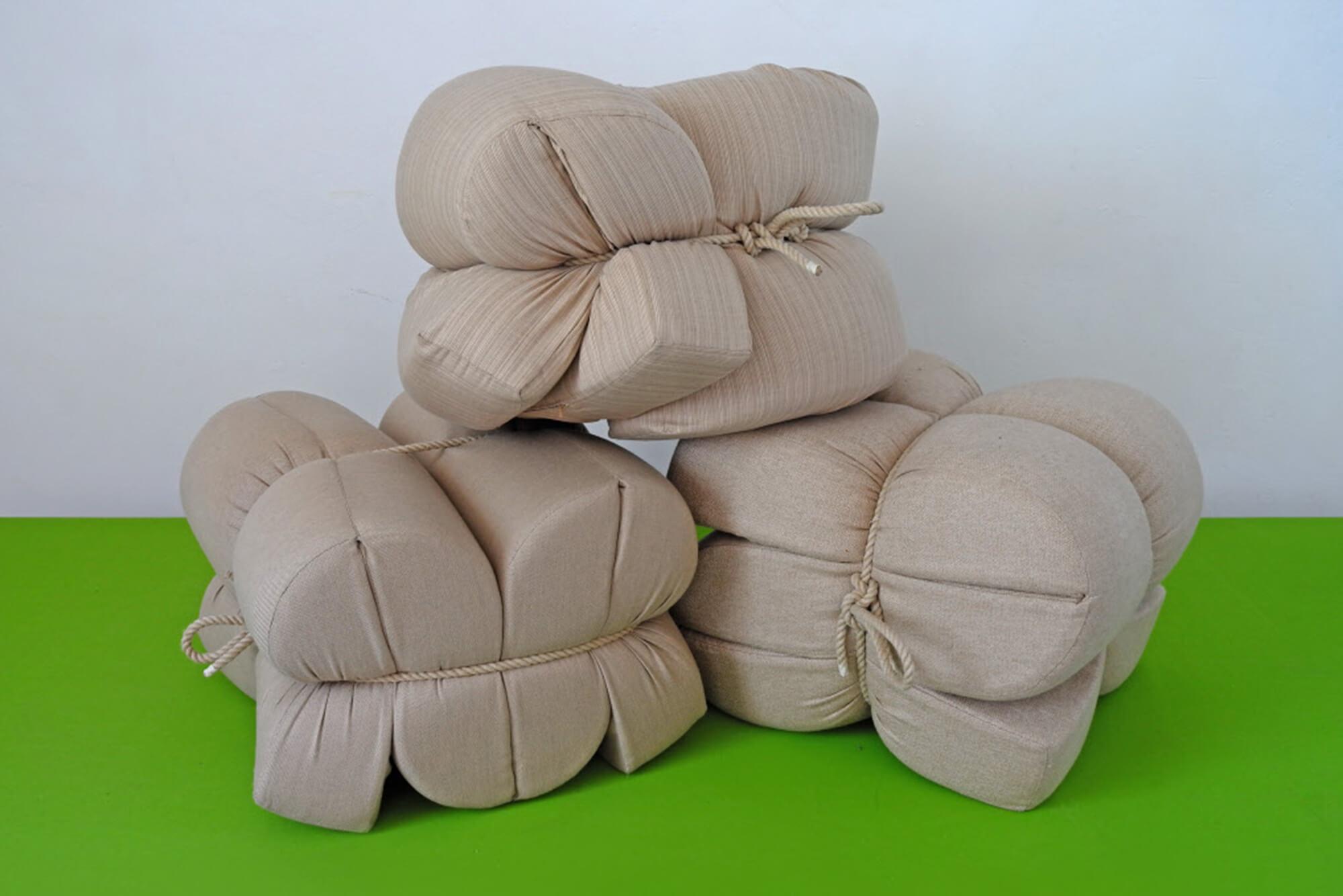 Almofadas feitas com tecidos Sunbrella bege são dobradas e amarrada com corda