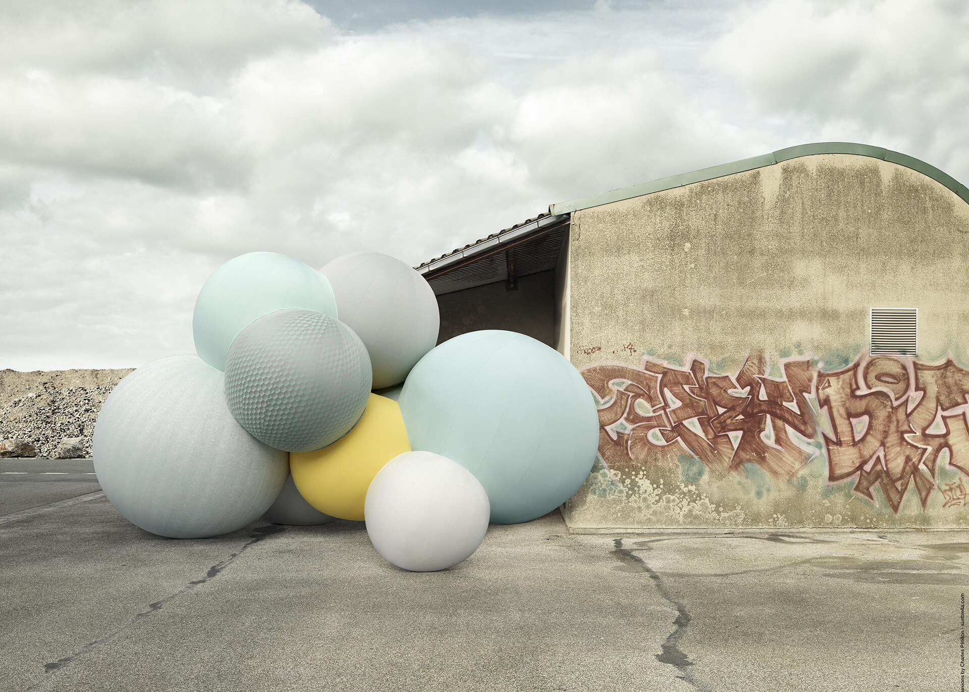 Sunbrella Connexions balloons by artist Charles Petillon are placed in an urban setting in front of a concrete building.