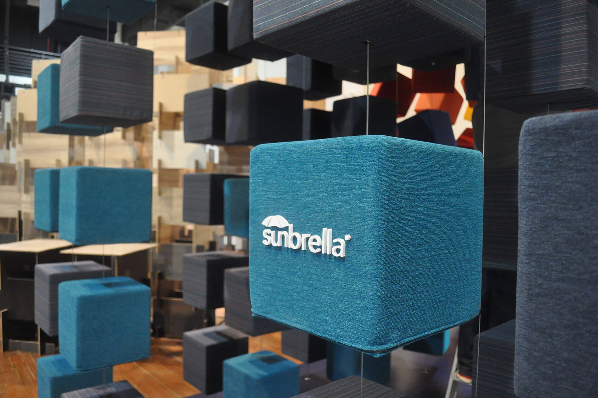 Close up of teal colored cubes upholstered in Sunbrella fabrics at the Singapore InDesign show.