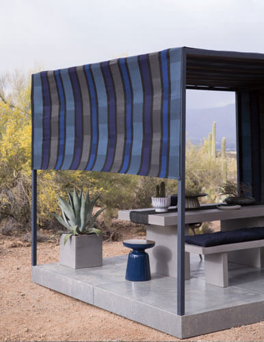 Outdoor shot in the Arizona desert featuring a modern pergola set up with Sunbrella shade fabric over a dining table and benches.