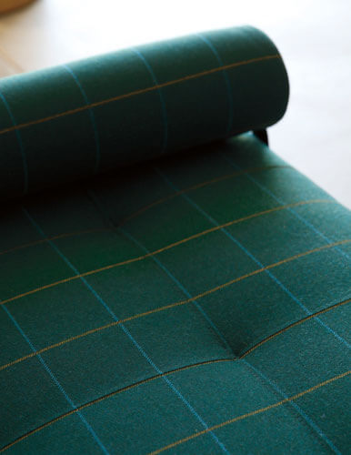 Close-up of a sofa cushion and armrest, covered in dark green checked Sunbrella upholstery fabric.