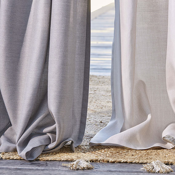 Drapery made of grey Sunbrella fabric hanging outside.