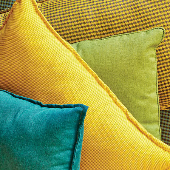 Pillows in bright yellow, green, and teal Sunbrella fabrics.