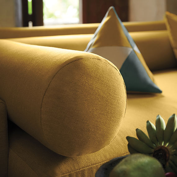 Close up of corner of yellow sofa and yellow bolster pillow.