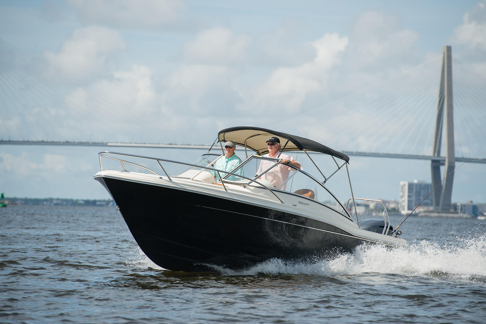 Power boat with Bimini made with black Sunbrella Supreme fabric with bridge in background