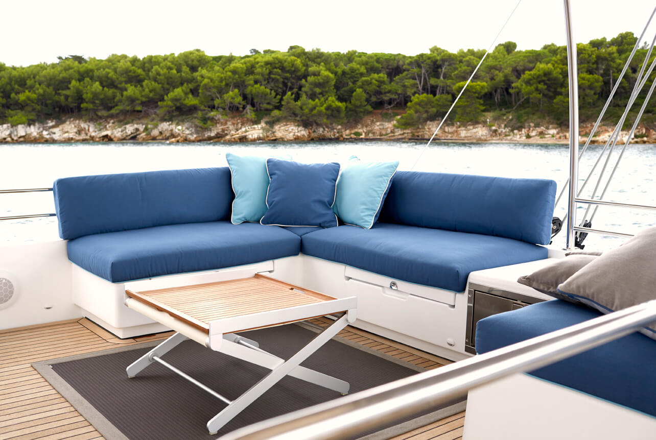 Exterior seating area on a catamaran with cushions covered in blue Sunbrella fabrics