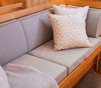 A boat cabin has added color and pattern with throw pillows made using Sunbrella fabrics