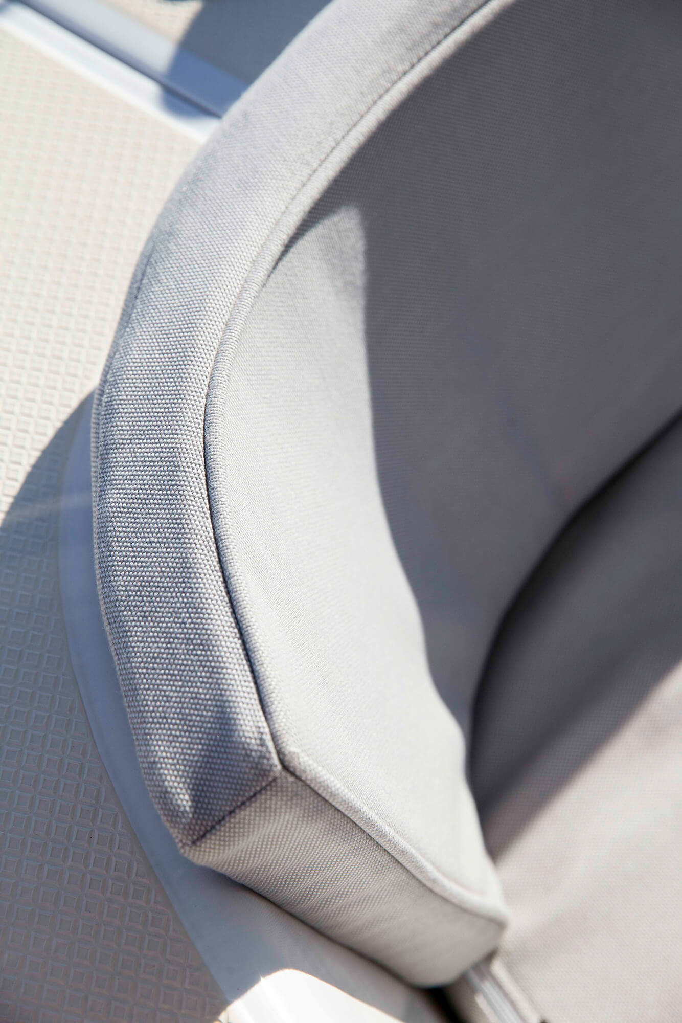 Detail shot of a boat seat cushion and back made using beige Sunbrella upholstery fabric