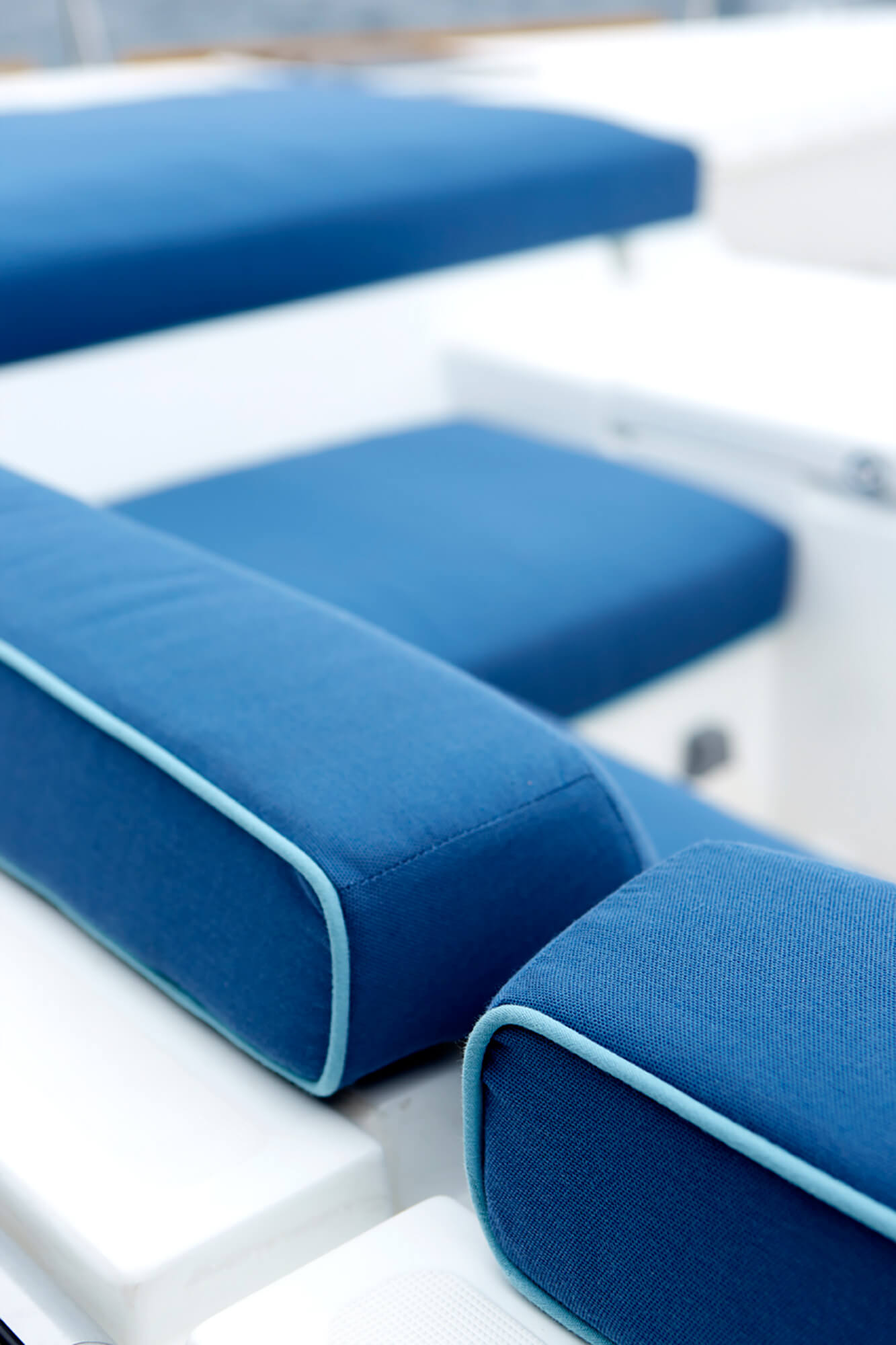 Detail of blue cushions with light blue piping on boat seat cushions