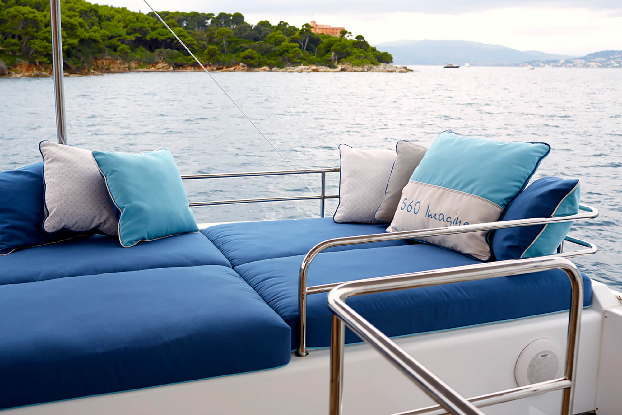 Blue cushions and pillows made using Sunbrella fabric with water scenery in background