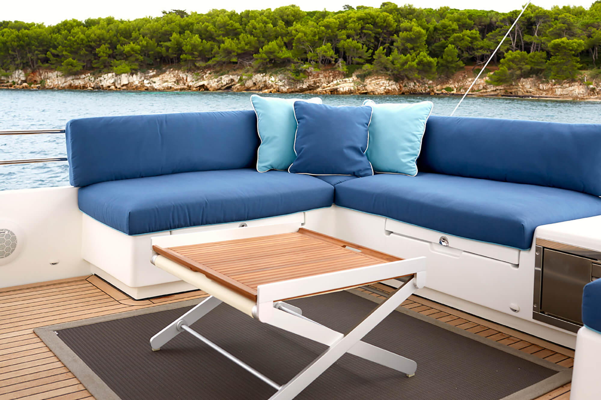 Cushions and Pillows made using different hues of blue Sunbrella upholstery fabrics on seating on the exterior of a catamaran