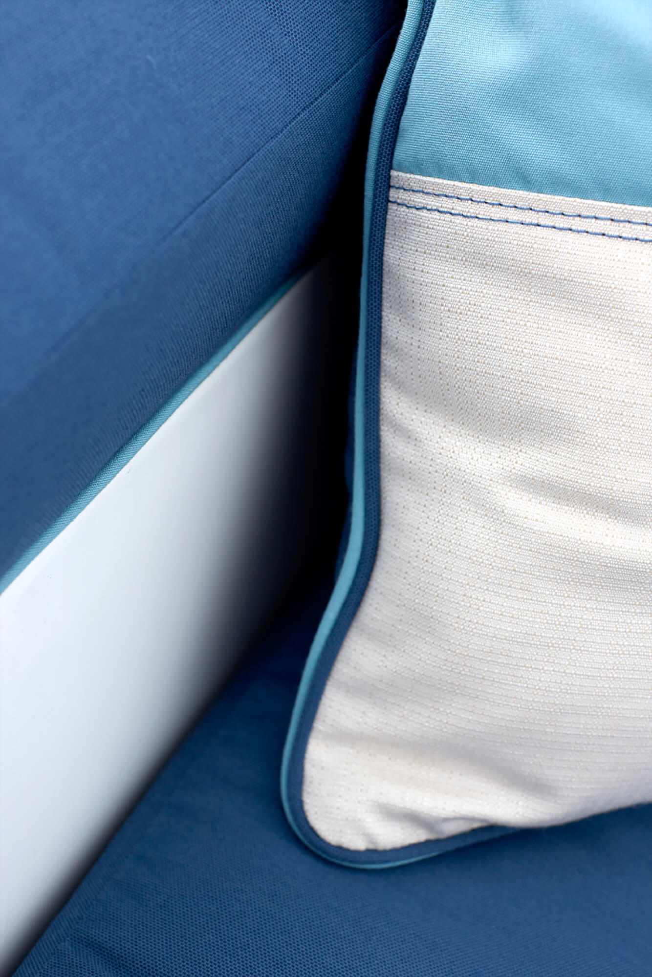 Detail photo of pillow with blue and white fabrics sitting on a blue cushion.