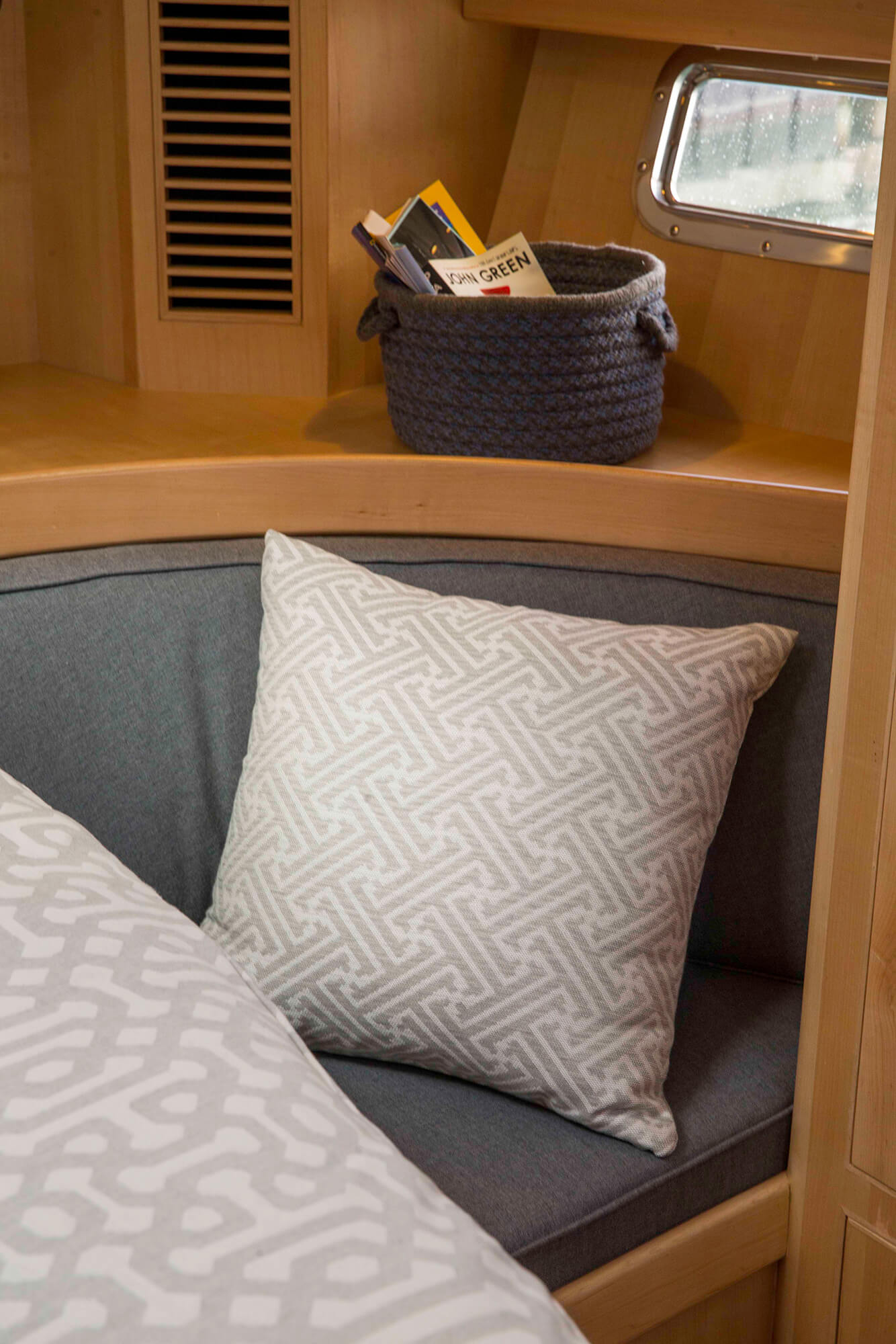 A grey patterned pillow on a cushion in the cabin of a sailboat