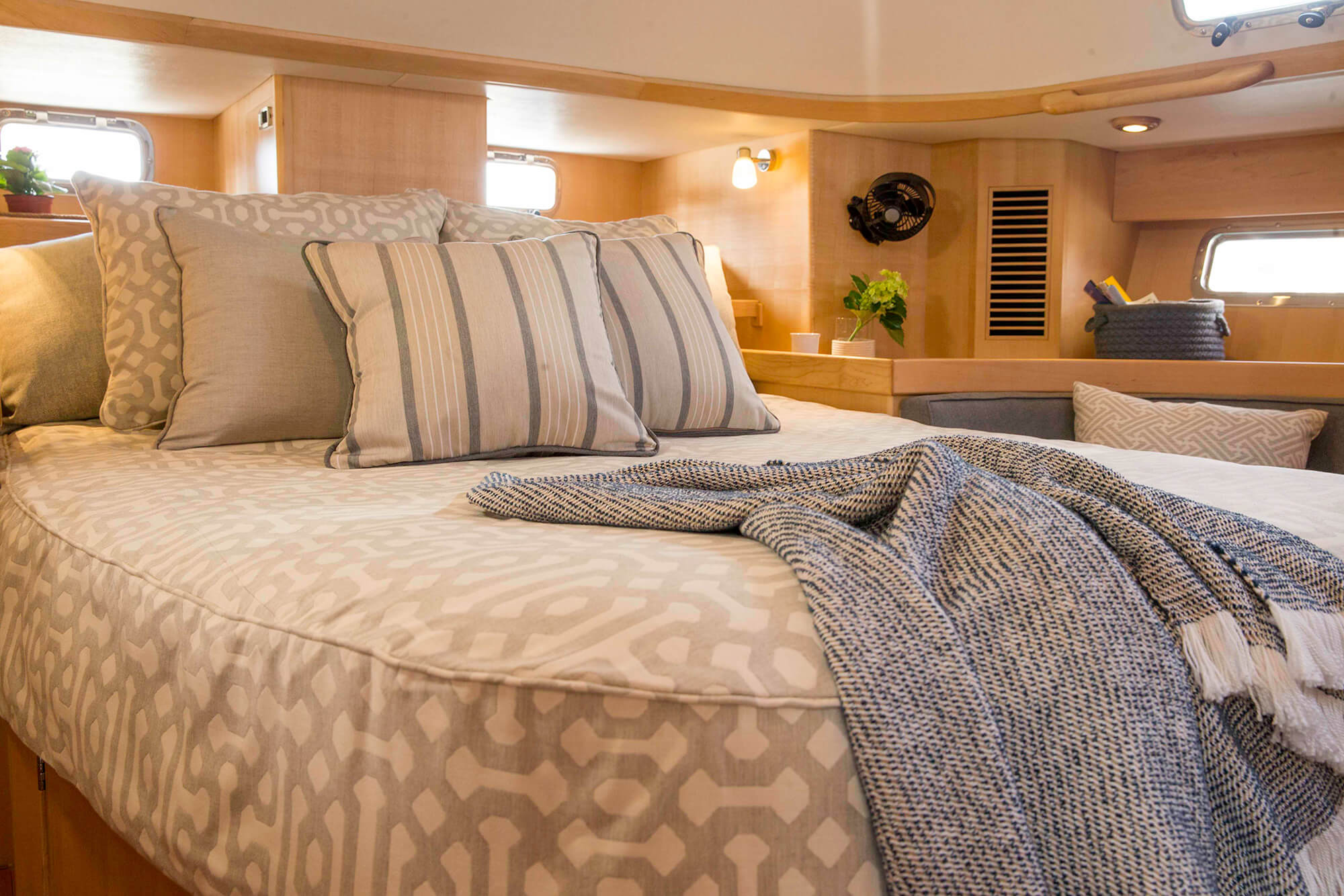 A bed on a sailboat is covered in Sunbrella upholstery fabric Fretwork Pewter with coordinating throw pillows