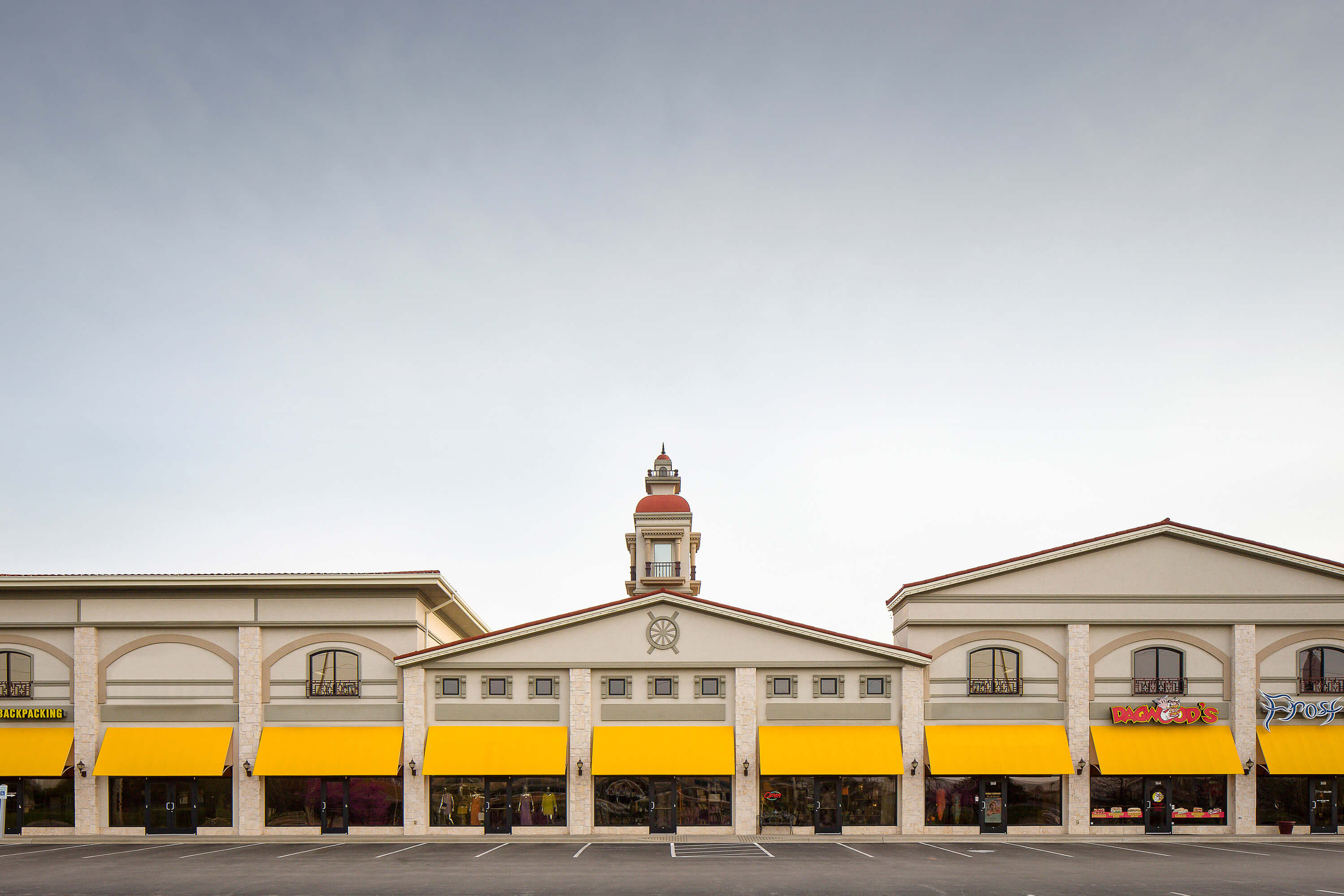 Yellow Fixed Frame Awning Made With Sunbrella Clarity Fabric At Shopping Center