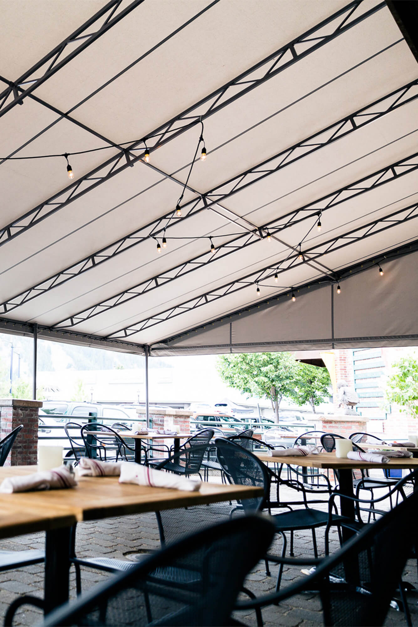 Fixed Frame Awning With Beige Sunbrella Fabric Covering Restaurant Patio