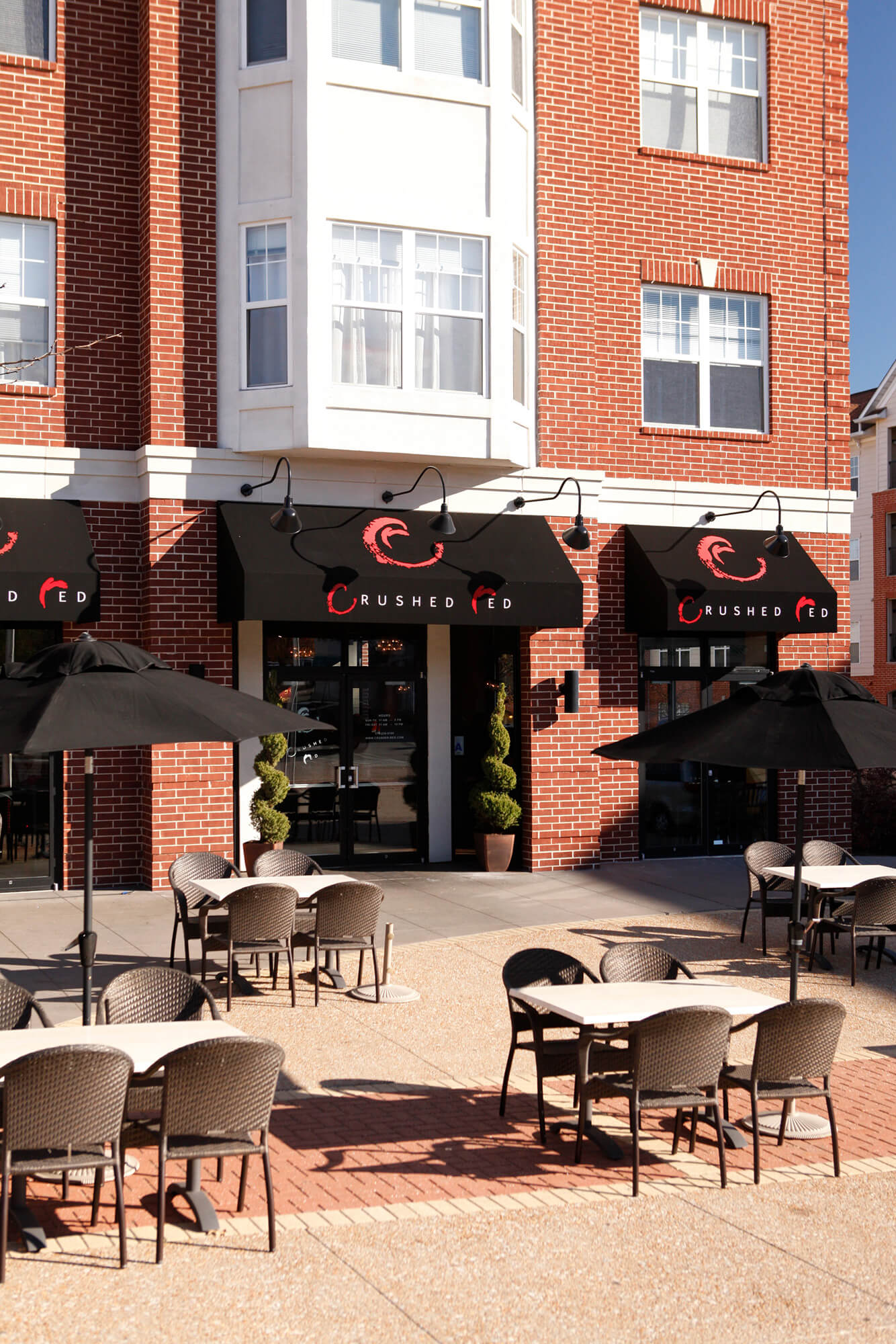 Fixed frame awnings with SGS logos and black umbrellas outside a restaurant