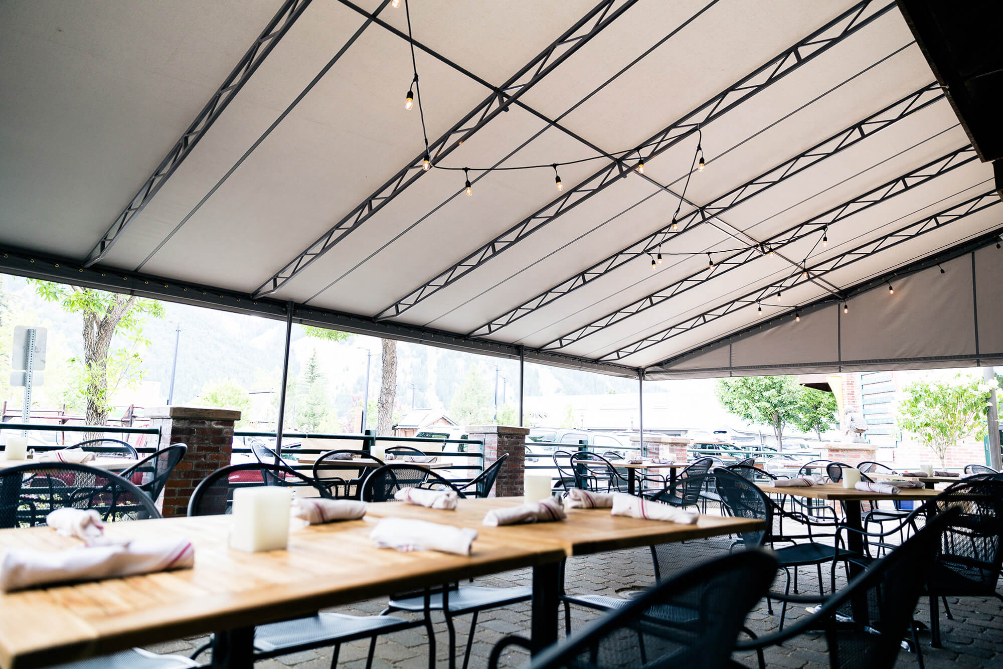 Fixed frame awning with beige Sunbrella fabric shading restaurant patio