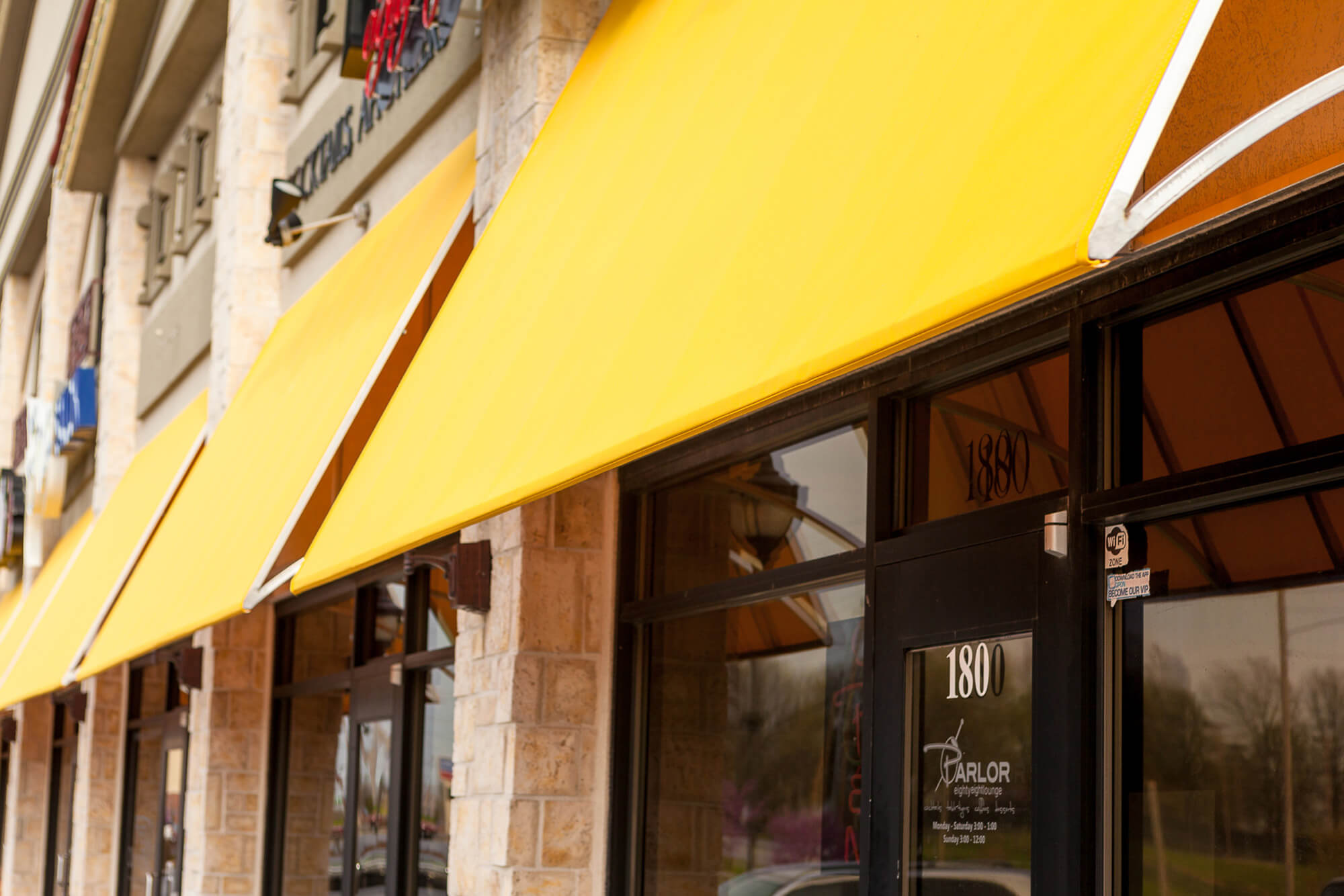 Storefront adorned with fixed frame awnings made using yellow Sunbrella fabrics
