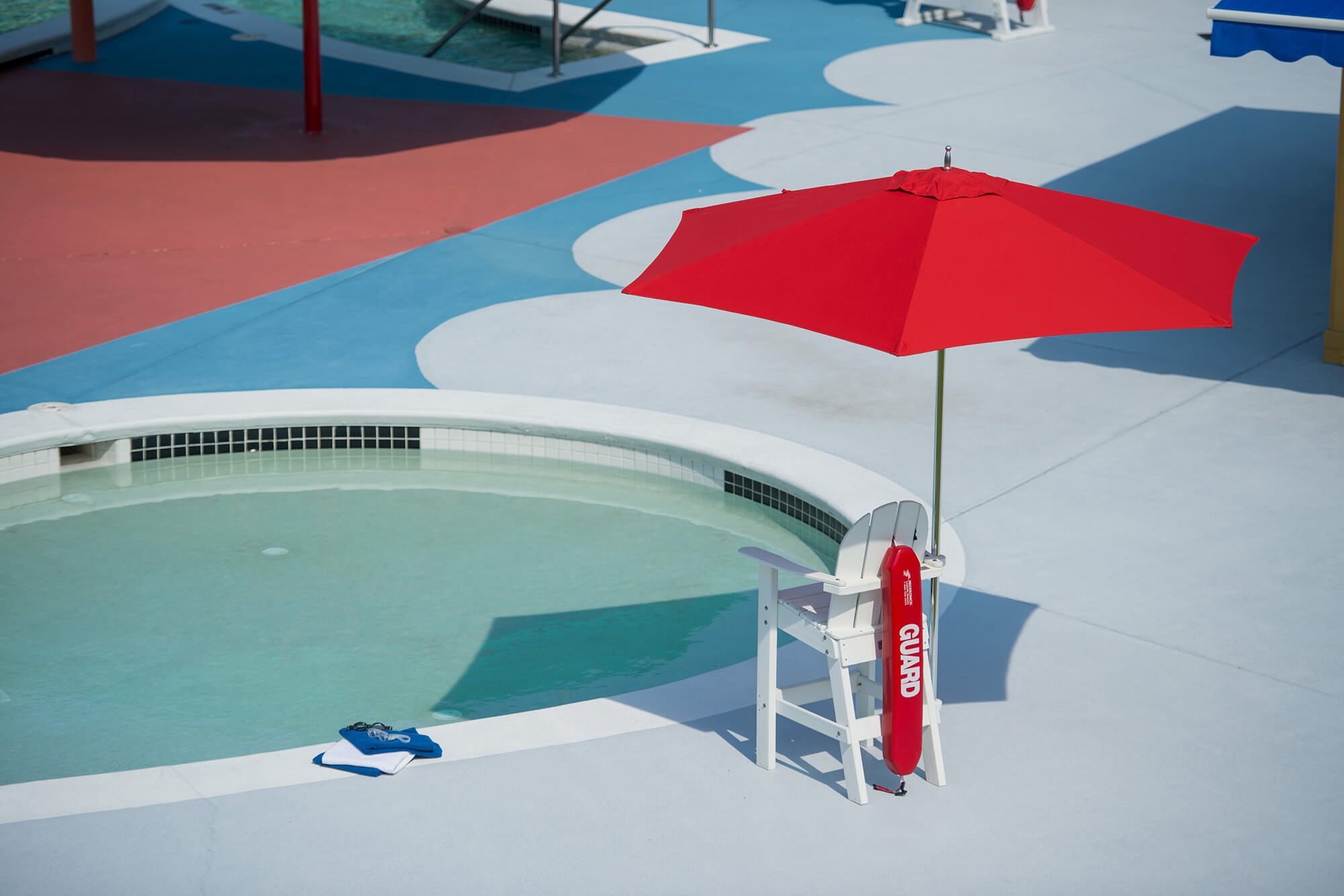 A red umbrella with Sunbrella fabrics shading a lifeguard chair