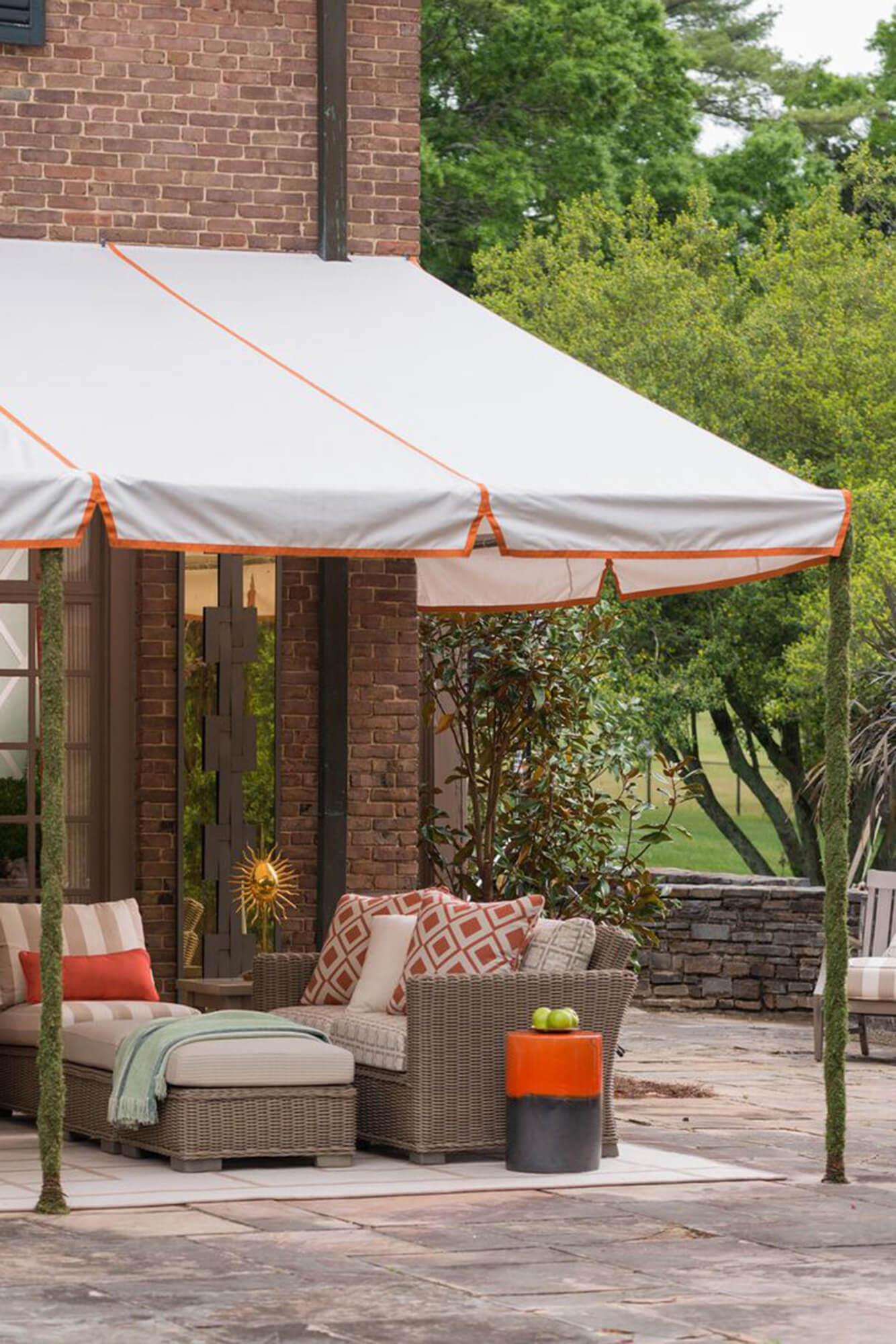 Patio covered with a fixed frame awning with white Sunbrella fabric and orange detailing