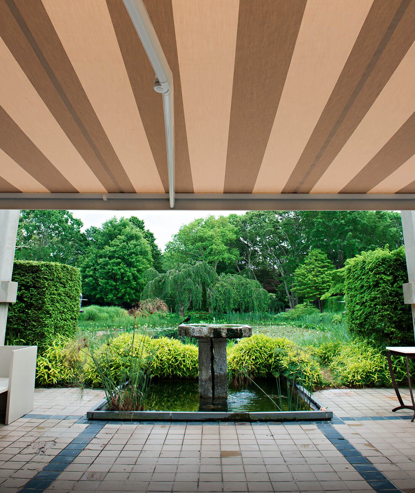 Outdoor Garden Shaded By Retractable Awning With Striped Beige Sunbrella Fabric