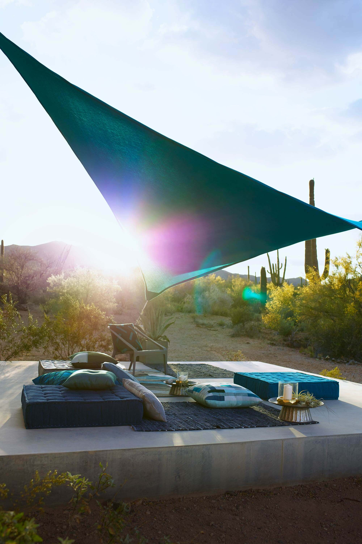 청록색 Sunbrella Contour 직물을 사용하여 만든 돛형 차양으로 가렸으며 바닥 베개가 놓인 실외 자리