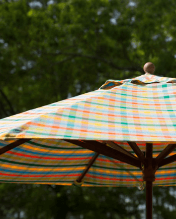 A market umbrella with a bright plaid fabric from the Sunbrella Shift collection