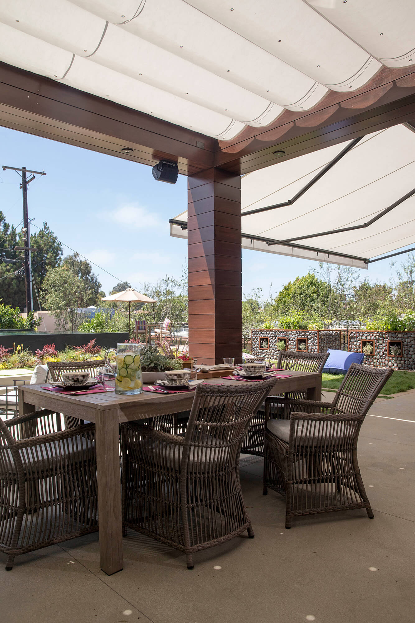 An outdoor patio is covered by a pergola and retractable awning made using silver Sunbrella fabric