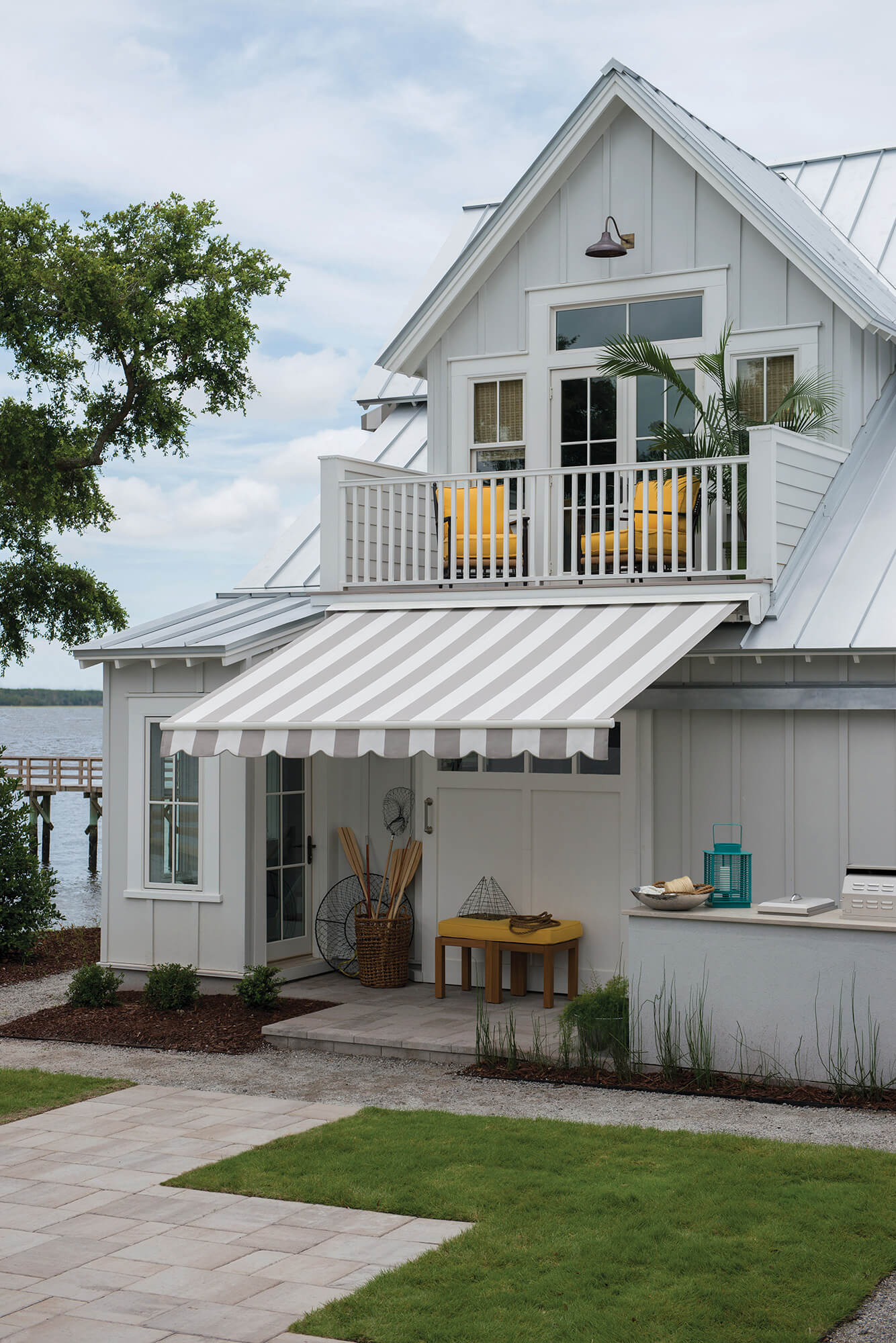 Coastal home with grey and white striped awning made using Sunbrella fabric