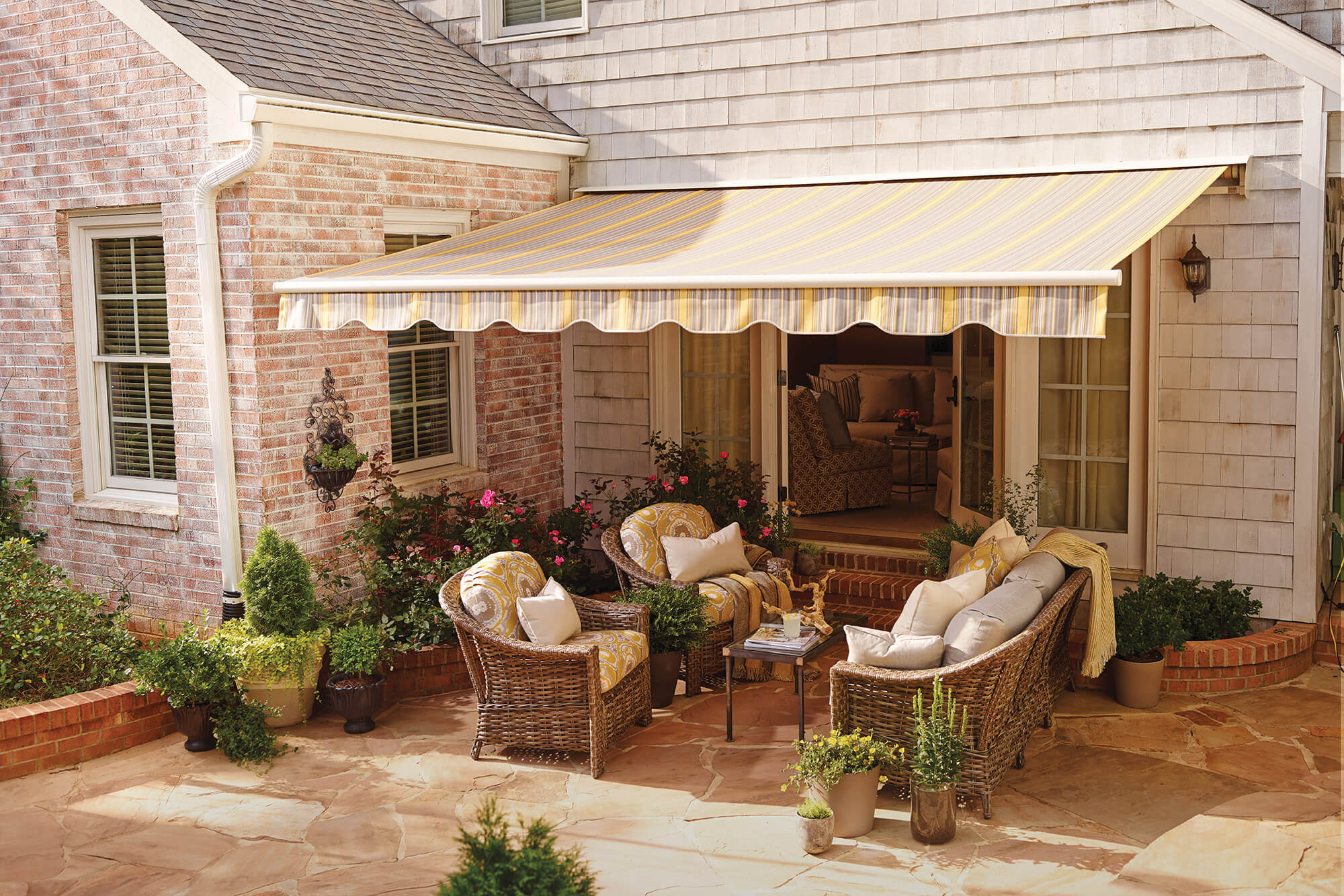 Seating area on a patio shaded by a yellow striped retractable awning