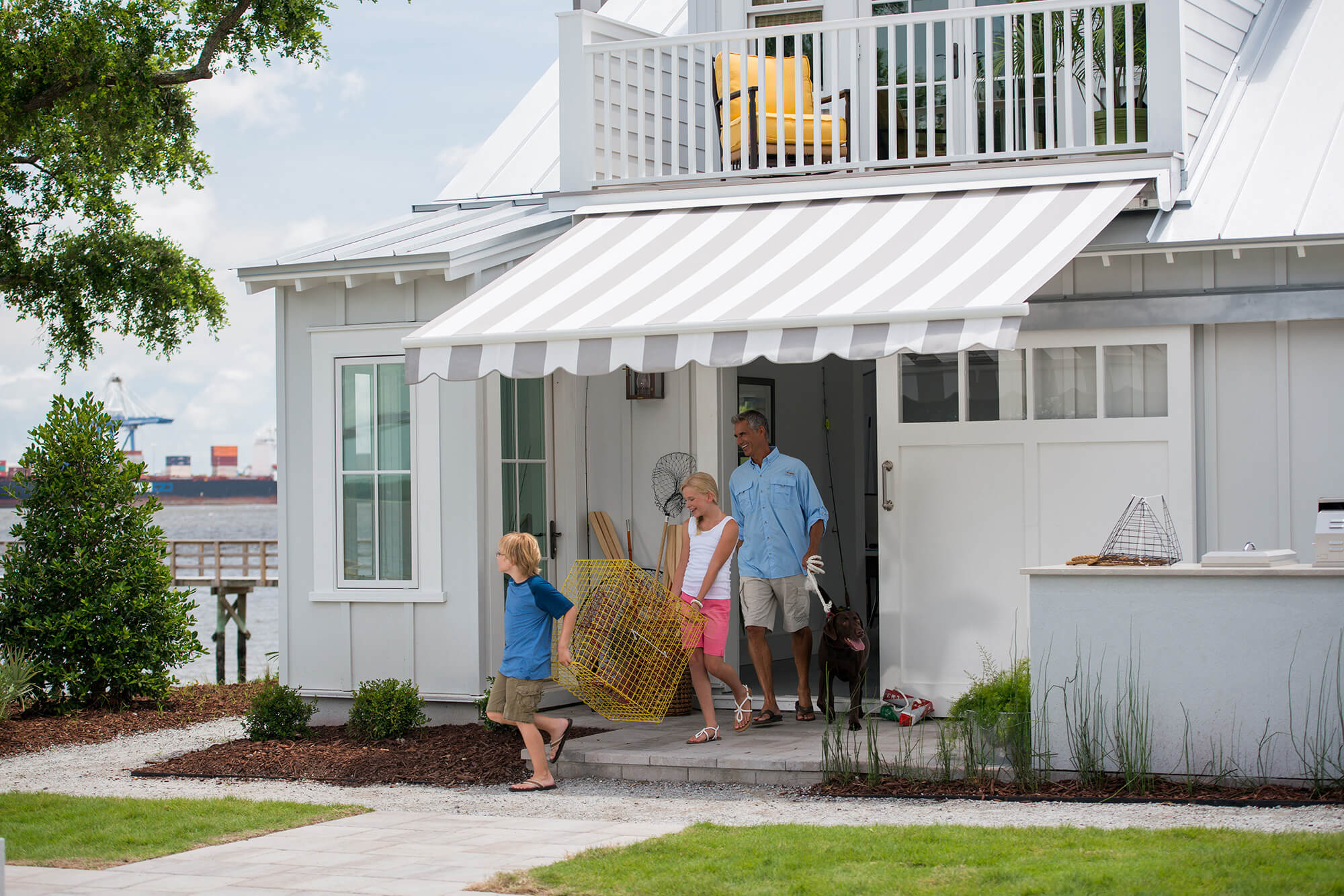 Family walking under grey and white striped retractable awning