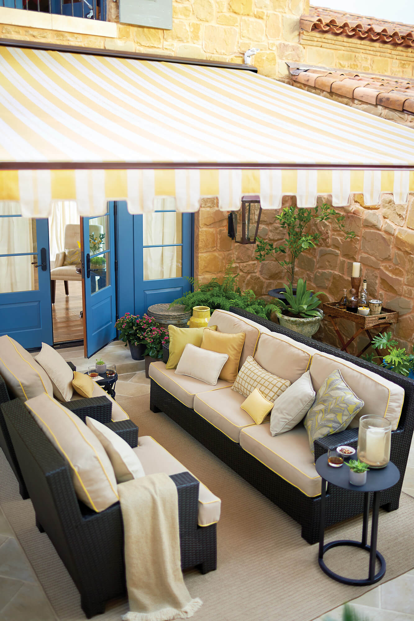 Patio furniture shaded by retractable awning made using yellow and white striped fabric